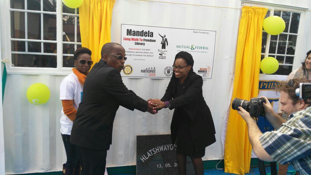 Busisiwe Sithole Mutual & Federal Head of Responsible Business handing over the library to the Principal Mr Hlatshwayo